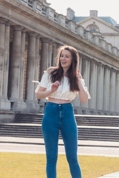 Rochelle is standing in front of some colonnades wearing high-waisted skinny jeans and an off-shoulder white cropped top. She is playing with her hair and laughing while looking off camera.
